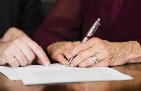 Starsza kobieta podpisująca dokument